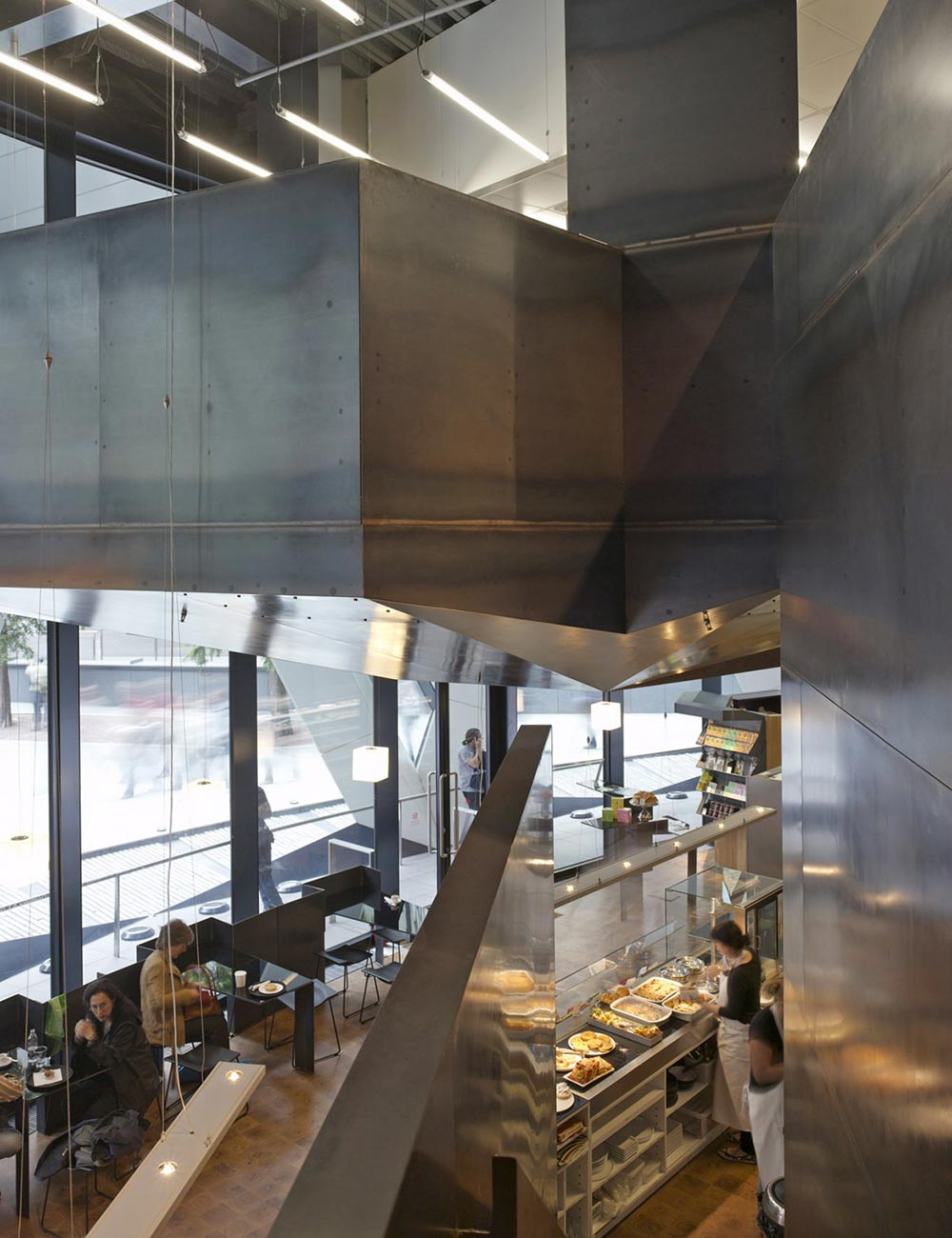 A shop, café and specialist kitchen are accommodated within the double-height ground floor space behind the entrance to 30 St Mary Axe. A new commercial kitchen level is suspended from the ceiling creating a striking, sculpted steel ceiling to the café level below. Both the mezzanine and stair are fabricated from 3mm steel panels. Steel is also used for furniture, while warmth is added by an end-grain oak floor and distinctive glass panels, back painted in a rich purple hue that allows the seamless integration of the client's established brand. We provided all mechanical and electrical services.